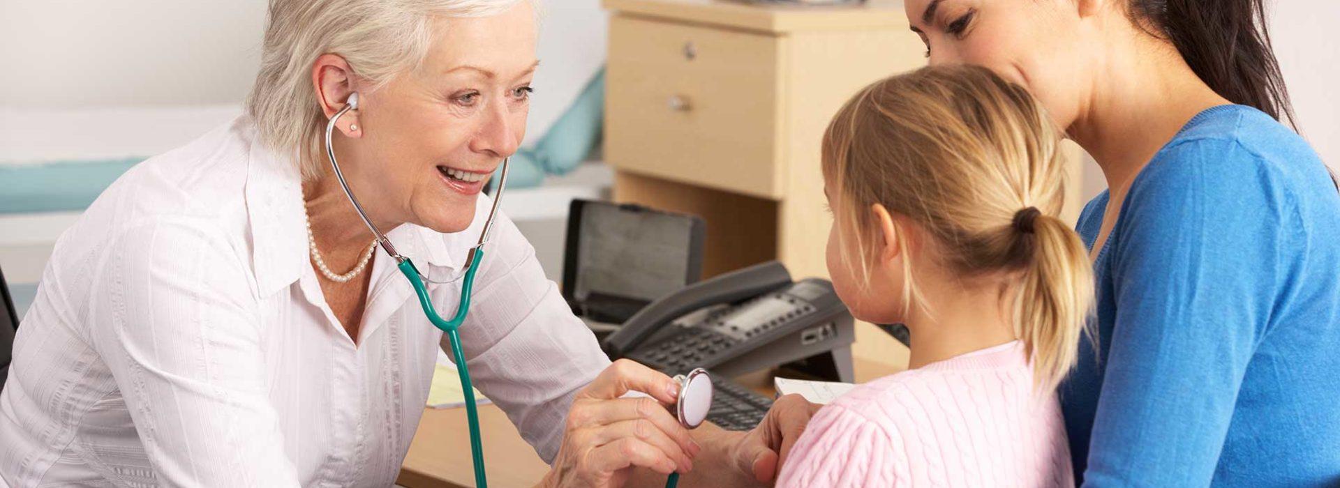 female doctor using stethoscope on little girl in her mum's lap