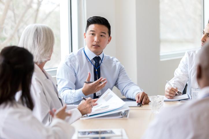 Serious hospital executive talks during meeting